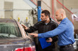 auto service, repair, maintenance and people concept - mechanic with clipboard and customer or car owner at workshop