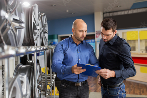Fridge magnet business, maintenance and people concept - male customer choosing alloy wheel rims and salesman with clipboard at car repair service or auto store