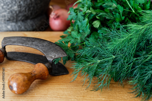 Rustic double blade mezzaluna herb cutter on wood board next to a large bunch of fresh herbs.