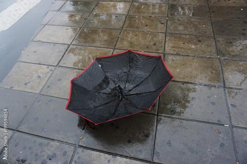 Primer plano de un paraguas roto en la calle.