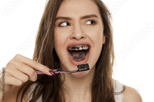 young woman brushing her teeth with a black tooth paste with active charcoal, and black tooth brush on white background