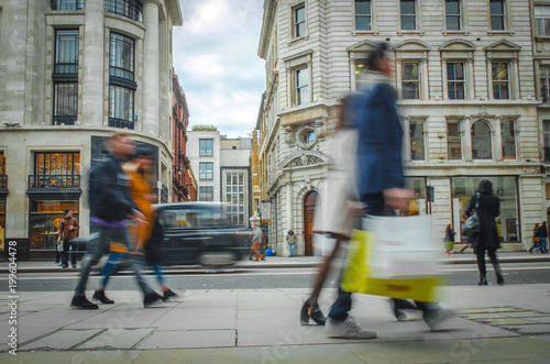 Motion blurred shoppers on busy high street carrying shopping bags - 199604478