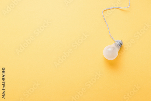 Light bulb on pastel yellow background top view, flat lay with copy space