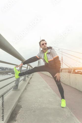 Fototapeta Urban jogger stretching on a bridge above the river.