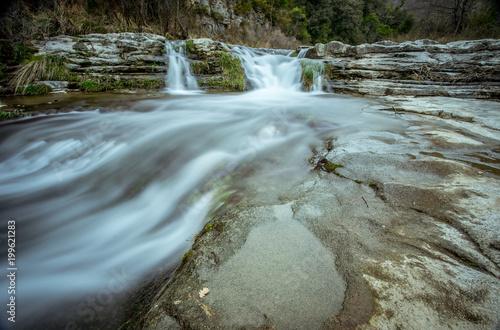 une cascade et une rivière qui coule sur des rochers  - 199621283