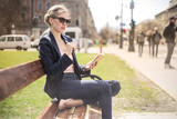 Fashionable woman sitting on a bench - 199622473