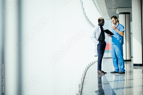 Medical Multiethnic Staff Having Discussion In A Hospital Hallway Two Doctors Working