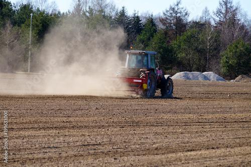 Fotobehang Trekker Spring field work. The act of harrowing the field for cultivation