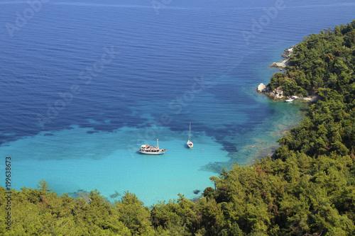 Biała łódź i jacht, błękitne morze, zatoka i pływacy, zielone sosny - idylliczne wakacje letnie - wycieczka; tło, kopia przestrzeń.