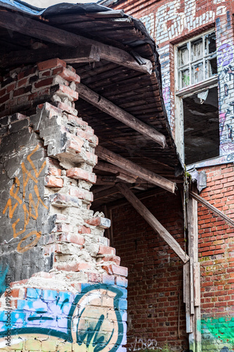 Fotobehang Graffiti Broken brickwall at abandoned factory building exterior
