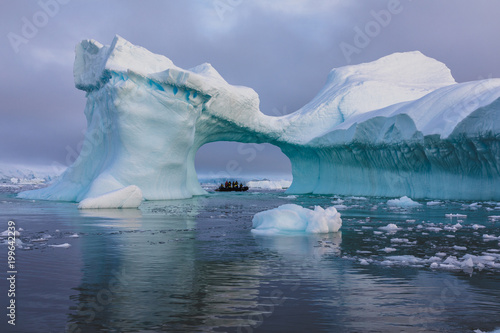 Fotobehang Antarctica A zodiac full of tourist viewed through an arch in a large iceberg, Antarctica