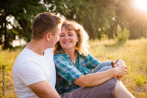 Outdoor portrait of smiling happy senior mother with her adult son