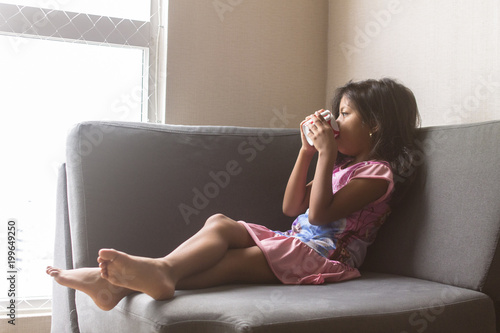 Little girl drinking coffee on the sofa