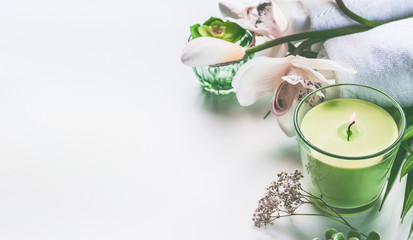 Green spa or wellness background with towels, candle, orchid flowers and accessories on white desk © VICUSCHKA