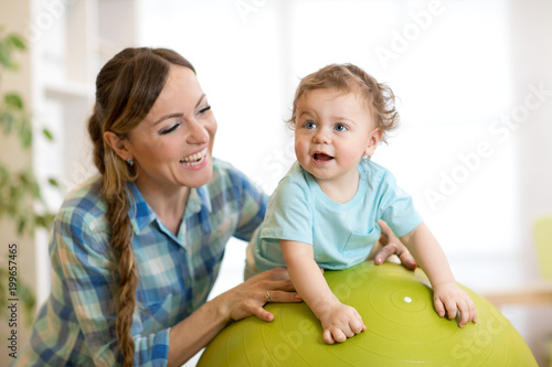 Poster Happy mother and baby toddler on fitness ball in nursery at home. Gimnastics for kids on fitball.