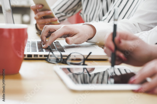 Young business team working on office desk with electronic devices