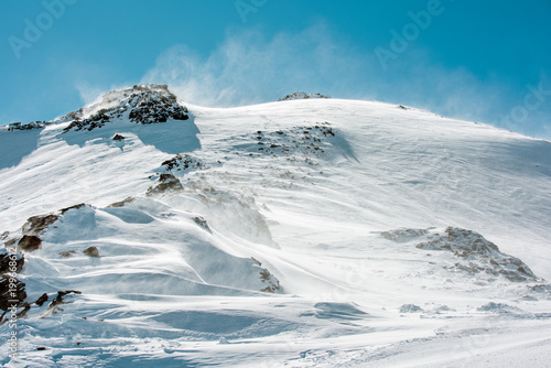 In de dag Blauwe jeans Mountain landscape. Snow-covered top of the mountain against the cloudless blue sky