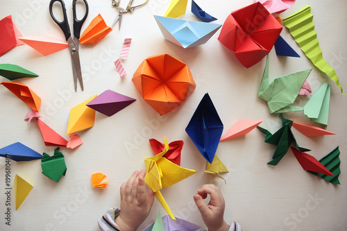 the child makes origami. Multicolored Origami and paper on  a white table. origami lesson © dyageleva