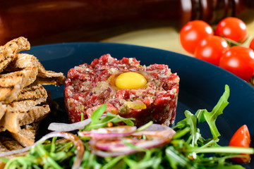 Dish with beef tartare, tomatoes and leaves in a restaurant, close-up