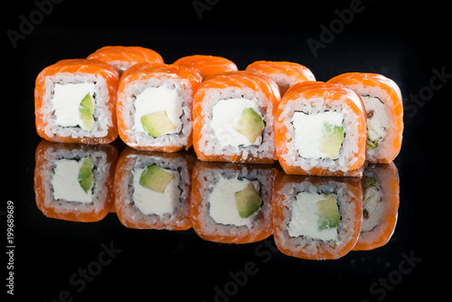 Delicious Philadelphia sushi rolls with rice, avocado, cream cheese and salmon on dark background