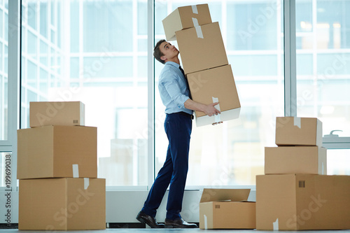 Fridge magnet Young businessman carrying huge stack of big boxes with office supplies during relocation to modern business center