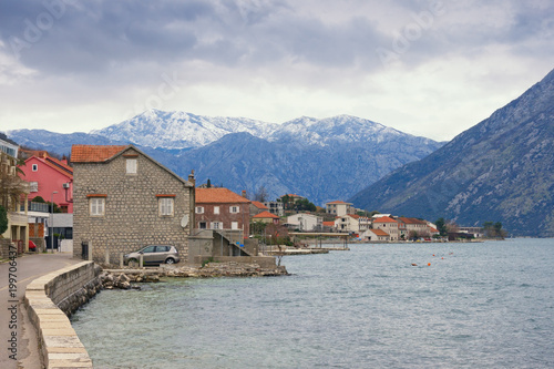 Plexiglas Donkergrijs Small Mediterranean town near snow-capped mountains on cloudy day. Montenegro, Bay of Kotor (Adriatic Sea), Prcanj