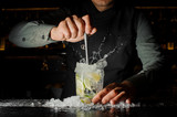 Bartender making cocktail at the bar counter - 199710253