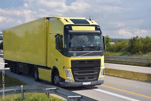 LKW auf einer Straße beim Transport von Waren - Logitsik und Spedition // Trucks on a road transporting goods - logistics and forwarding - 199721814