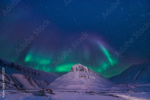Fotobehang Nachtblauw The polar arctic Northern lights aurora borealis sky star in Norway Svalbard in Longyearbyen city man mountains