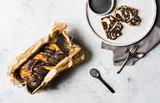 Mohnkuchen geschnitten und hübsch angerichtet auf weißem Holzteller mit Mohn in Schale und Mohnkuchen am Stück in einer Backform von oben bei tageslicht fotografiert