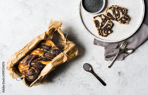Foto op Aluminium Klaprozen Mohnkuchen geschnitten und hübsch angerichtet auf weißem Holzteller mit Mohn in Schale und Mohnkuchen am Stück in einer Backform von oben bei tageslicht fotografiert