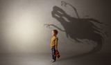 Scary ghost shadow in a dark empty room with a cute blond child  - 199746208