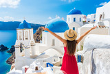 Europe travel happy vacation woman. Girl tourist having fun with open arms in freedom in Santorini cruise holiday, summer european destination. Red dress and hat person. - 199751065