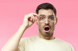 Casual dressed young man in beige t-shirt shouting oh my god with open mouth, surprised by low price and sales, holding transparent glasses, isolated on pink background