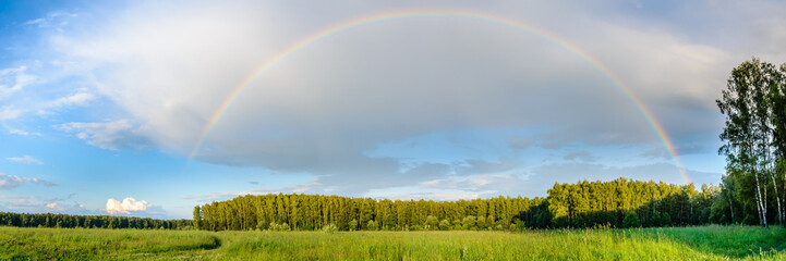 Summer panorama with a semicircle of a rainbow