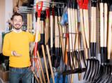 Male customer examining pitchforks - 199761413