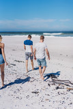 Group of young friends walking barefoot on a beach