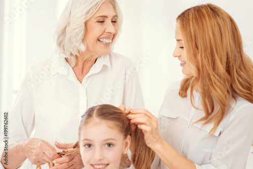 Foto op Plexiglas Kapsalon Fun and joyful moment. Selective focus on an excited beautiful elderly lady grinning broadly while talking to her mature daughter and making ponytails for her cheerful granddaughter.