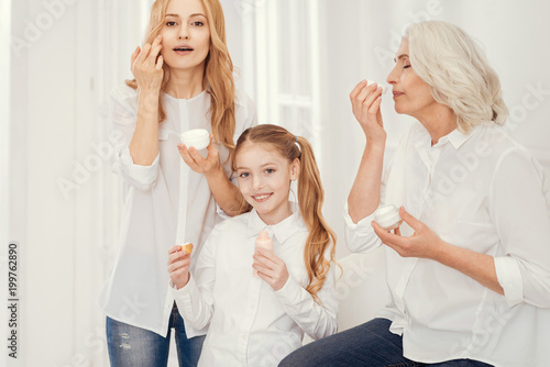 Skincare treatment. Three generations of women sitting next to each other while spending girly time together and taking care of their face skin