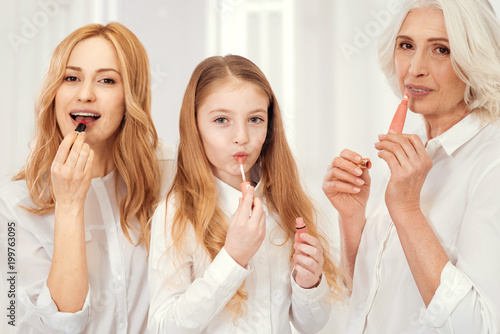 Every girls routine. Three generations of women looking into the camera while spending a girly together and applying lipstick and lip glosses at home.