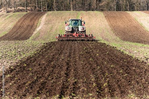 Fotobehang Trekker Traktor beim Grubbern der Ackerfläche - 1452