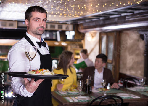 Portrait of male waiter who is holding tray with order - 199766409