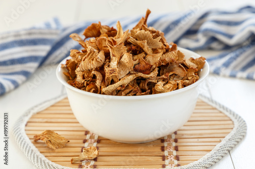 Dry chanterelles mushrooms in a white plate on a white wooden background - 199792831