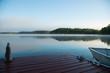 Muskoka dock and boat on a misty morning lake