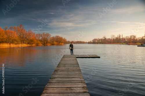 Plexiglas Pier Blonde girl on a wooden landing stage overlooking a lake at sunset in Braunschweig, Germany