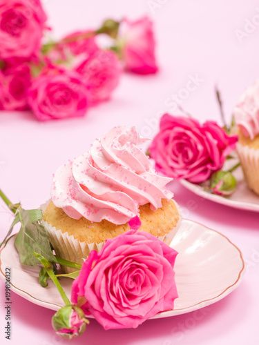 Cupcake with pink cream decoration and roses on pink pastel background. - 199806822