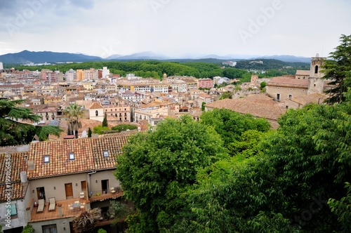 Fotobehang Blauwe hemel View of the city of Girona from the medieval pedestrian border wall. Roofs of houses, trees, mountains in a haze in the background. Cloudy sky. Girona, Spain