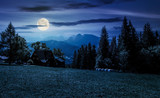 beautiful landscape of Tatra Mountains at night in full moon light. location Zakopane village, Poland. lovely scenery with forest on a grassy meadow and a ridge under the gorgeous sky in the distance