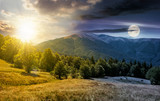 time change concept over the beech forest on grassy meadows in mountains. beautiful Landscape at the foot of Carpathian mountain Apetska with sun and moon