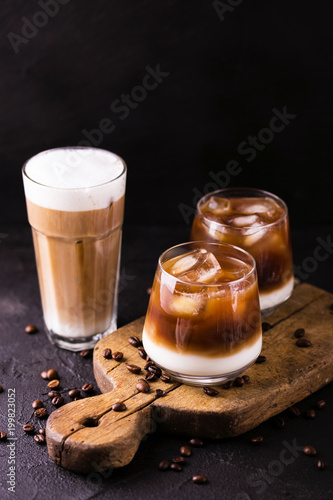 Iced coffee in glasses with milk. Black background - 199823052
